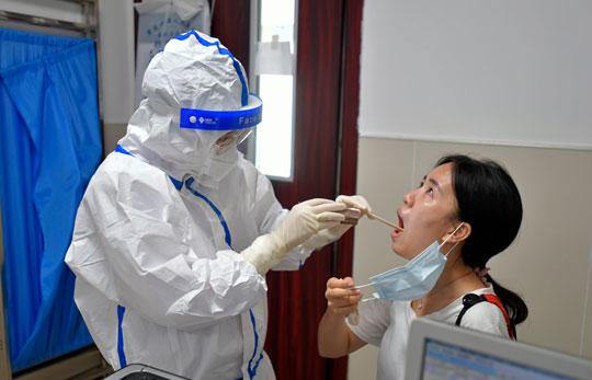 """""""全副武装""""的罗茜正在给一名患者做检查。.jpg"""