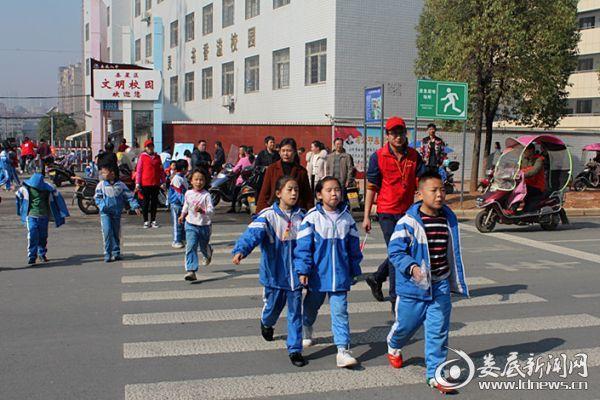 (放学时期,市卫计委党员志愿者在娄底八中护送孩子们过马路)