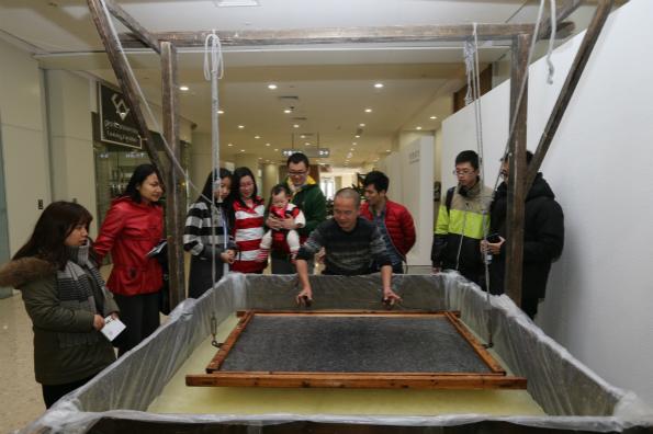 """参观者观看中国传统造纸术""""连四纸""""的制作工序"""