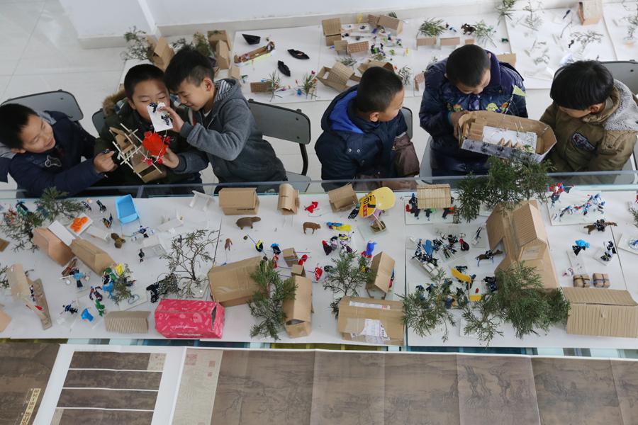 2014年12月7日,在湖北襄阳市襄城区青少年活动中心,小学生们在完善他们制作的立体版《清明上河图》。新华社发 王虎 摄   近日,襄阳第二十五中学小学部的五、六年级共400多名学生组成13个小组,利用包装材料、布头等生活中的平常物品,手工制作出立体版的《清明上河图》。立体版《清明上河图》与原画卷按4:1的比例呈现,孩子们自己动手制作出画卷中的人、牲畜、船只、房屋楼宇、轿子和树木等。