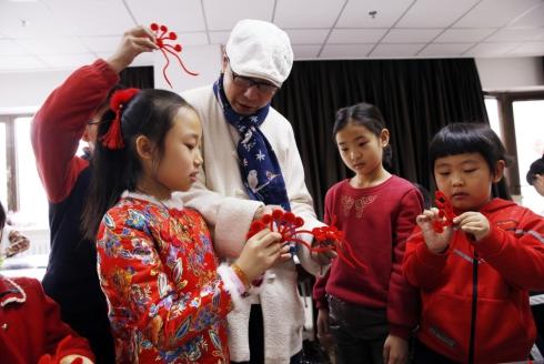 1月12日,非遗传承人在指导小学生制作绒花。.jpg