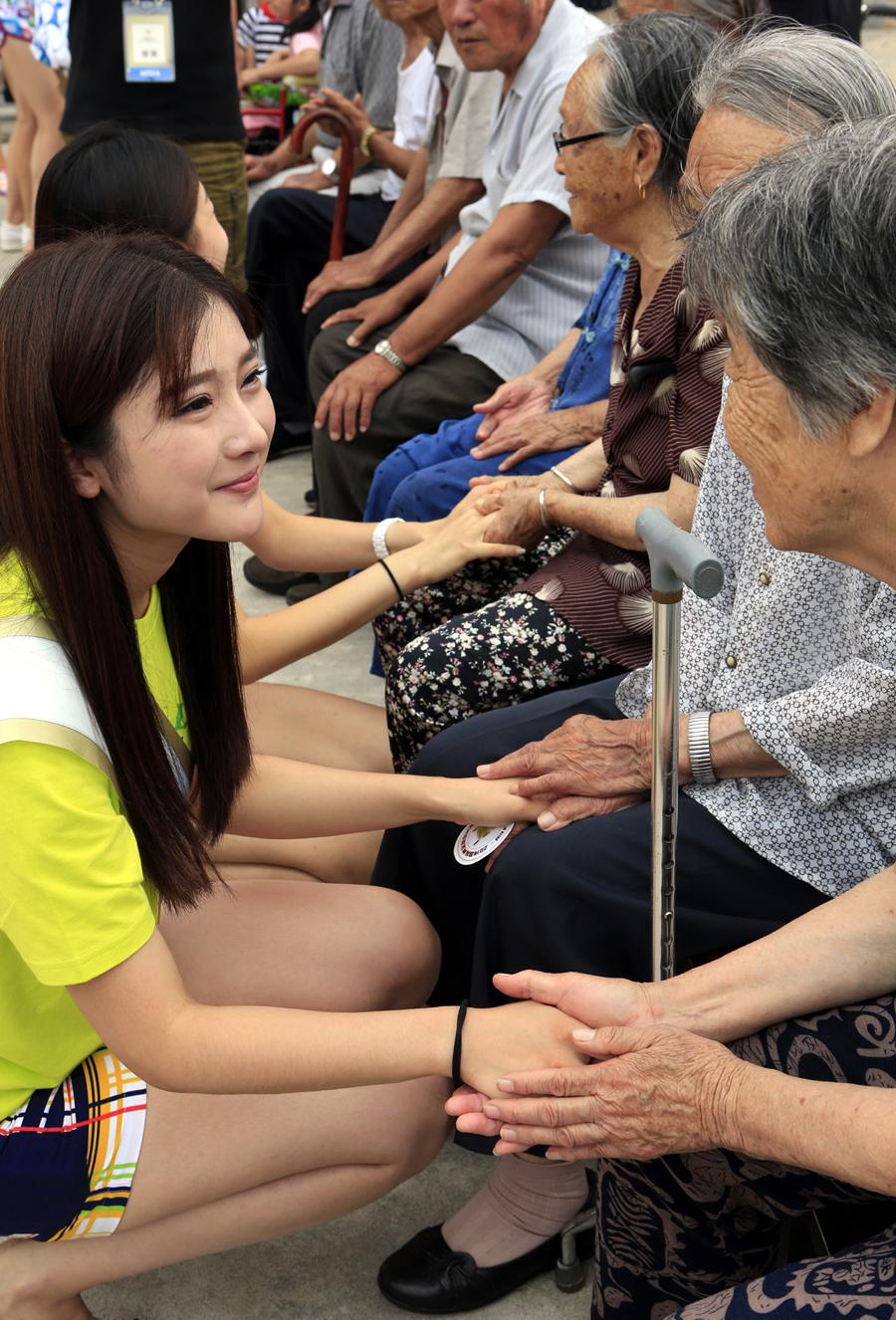 参赛模特在辽宁盘锦市社会(儿童)福利院与生活中这里的老人们聊天.