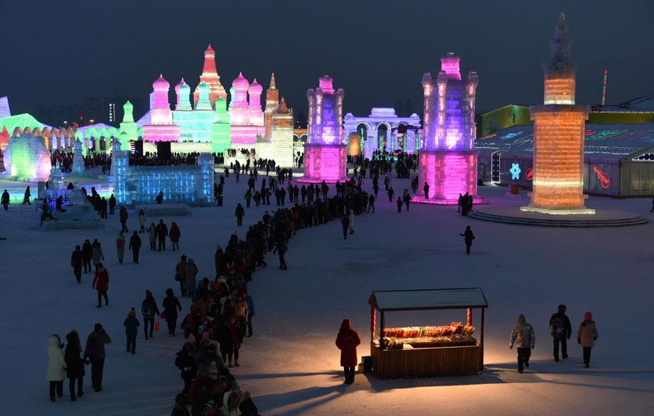 游客在哈尔滨冰雪大世界内排队体验冰滑梯