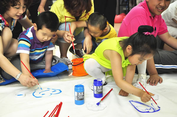 自闭症儿童和家长在联欢活动中现场作画.资料图片