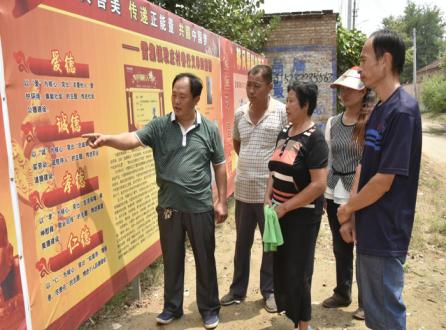 在四德榜前,付国然(左一)正在和村民交流.JPG