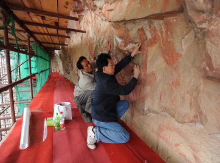图为朱秋平(前)带领同事在进行岩画描摹小.jpg