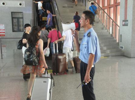 翁建忠在引导游客前往站台.jpg