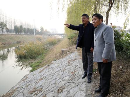 兰克平(左一)于村民一起查看水域附近安全情况。.jpg